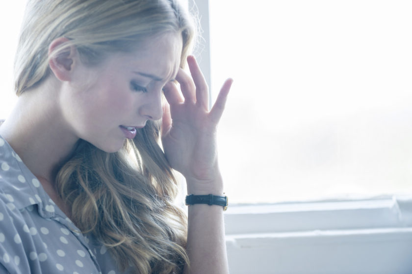 Woman looking upset or in pain. Attractive woman leaning against a wall with her hand on her forehead. She could be in pain, upset, angry, depressed or stressed. She is frowning and standing in front of a window. She is casually dressed. Copy space on right.